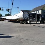 photo of wind turbine component being transported by truck