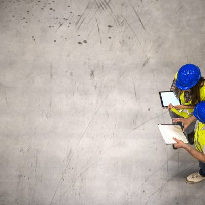 Top view of two construction workers wearing hardhats and reflective jackets holding tablet and checklist on gray concrete background. Group of engineers sharing ideas about the project.